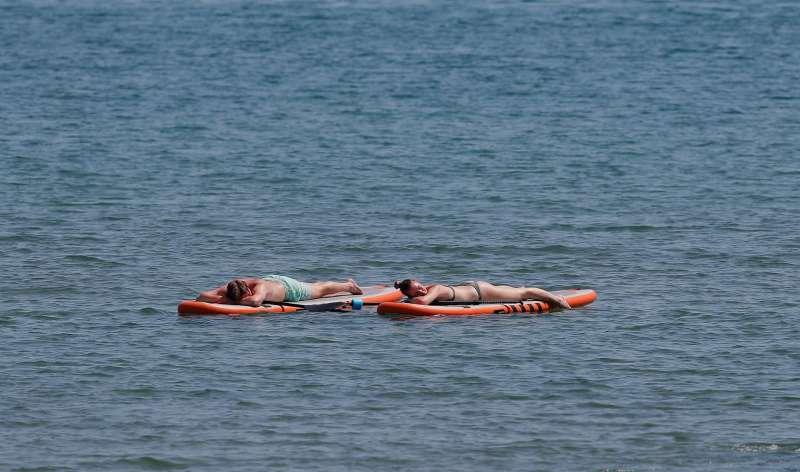 Una pareja disfruta del buen tiempo y de las altas temperaturas en la playa.