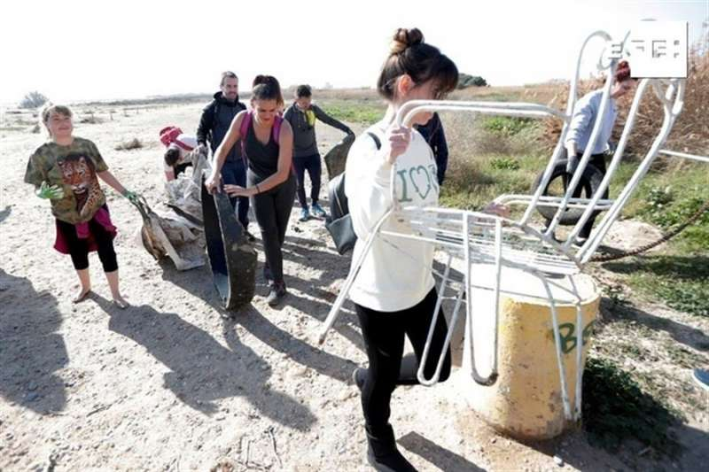 Varios voluntarios convocados por la asociación Ambiens sacan la basura encontrada junto a la marjal de Rafalell y Vistabella en la playa de Massamagrell.EFE/Kai Försterling