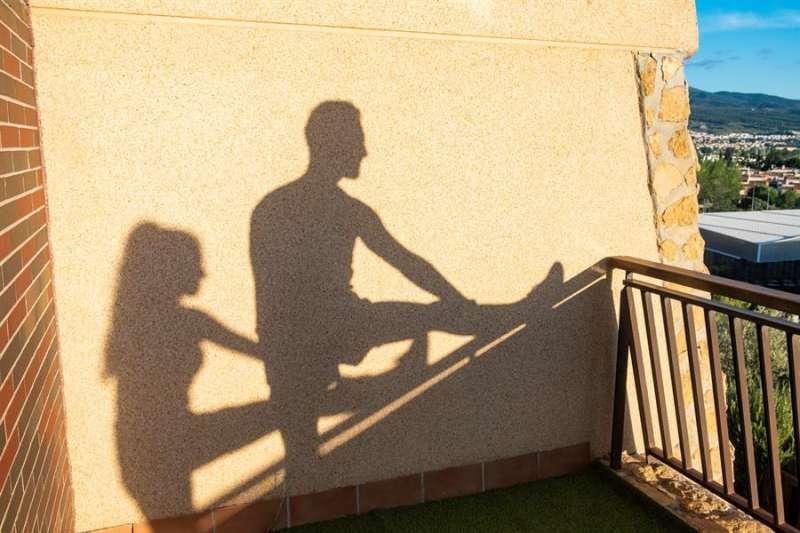 En la imagen, una pareja practica ejercicio en el balcón de su casa. EFE