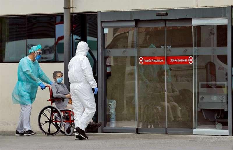 Dos trabajadores sanitarios trasladan a una mujer al servicio de urgencias del hospital La Fe de València. EFE