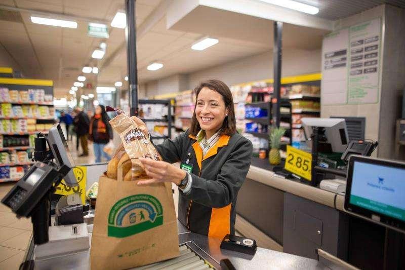 Una empleada de Mercadona empaqueta una compra en bolsas de papel