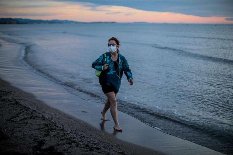 Una persona pasea a primera hora de la mañana por la playa de La Malvarrosa de València. EFE