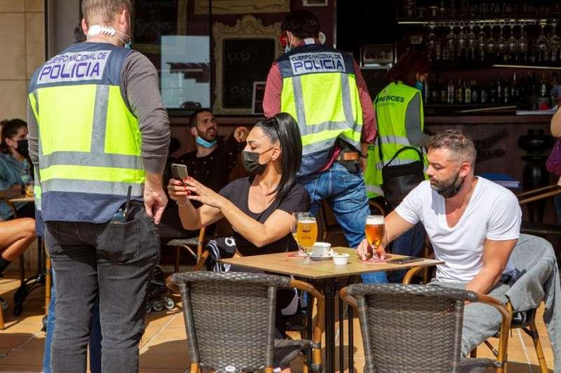 Miembros de la Policía Nacional vigilan que se cumplan las medidas anti Covid en una terraza. EFE/Archivo