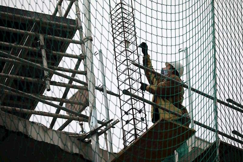 Trabajadores de la construcción protegidos con mascarillas durante su primer día de trabajo y retorno de actividades no esenciales tras la Semana Santa. EFE