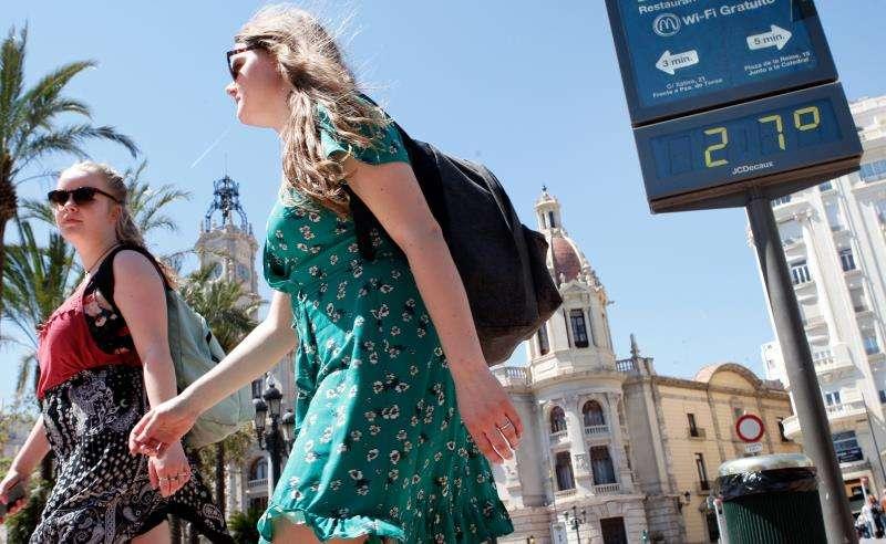 Dos jóvenes pasan ante un termómetro que marca 27 grados en el centro de València.EFE/Archivo