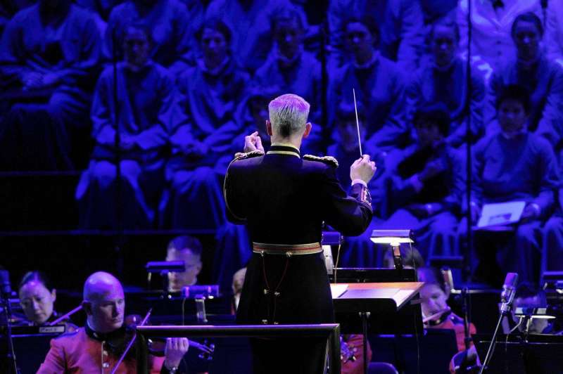 Imagen de un director de orquesta junto a un coro y una orquesta.