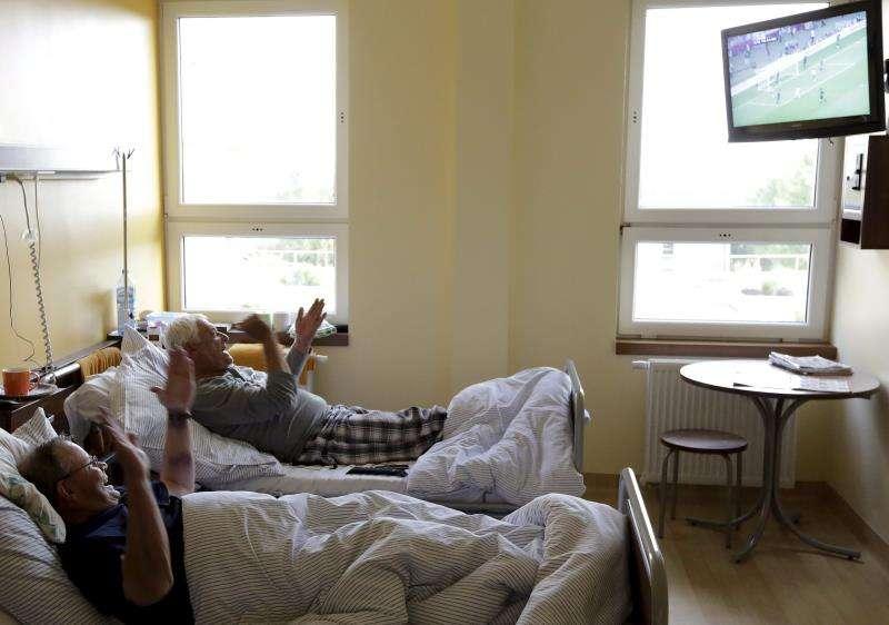Unos pacientes celebran un gol de su equipo de fútbol. EFE
