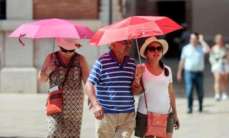 Unas personas se protegen del sol con parasoles. EFE/Archivo
