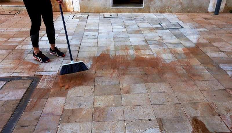 Una persona se afana en limpiar el barro depositado por la precipitación de polvo sahariano en Alicante. EFE