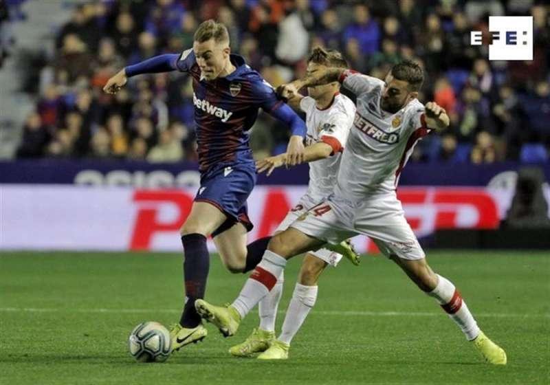 El defensa del Levante UD, Carlos Clerc (i), disputa el balón ante los jugadores del RCD Mallorca, Joan Sastre (c) y Daniel Rodríguez. EFE/Manuel Bruque.