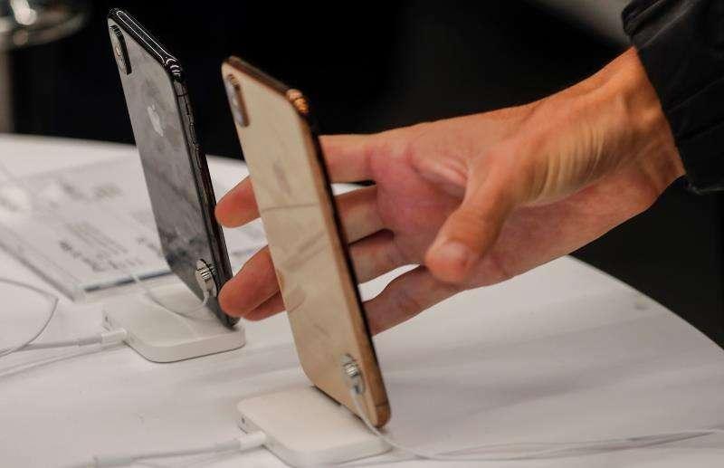 Una mujer se dispone a coger un iPhone. EFE/Archivo
