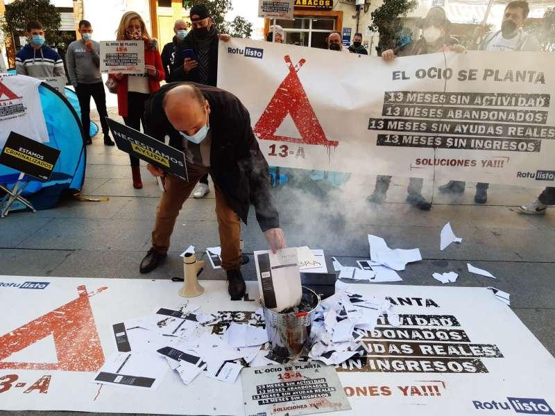 Quema de facturas, hace unos momentos, en la acampada en la plaza de Manises (Valencia) frente al Palau. / CEOH