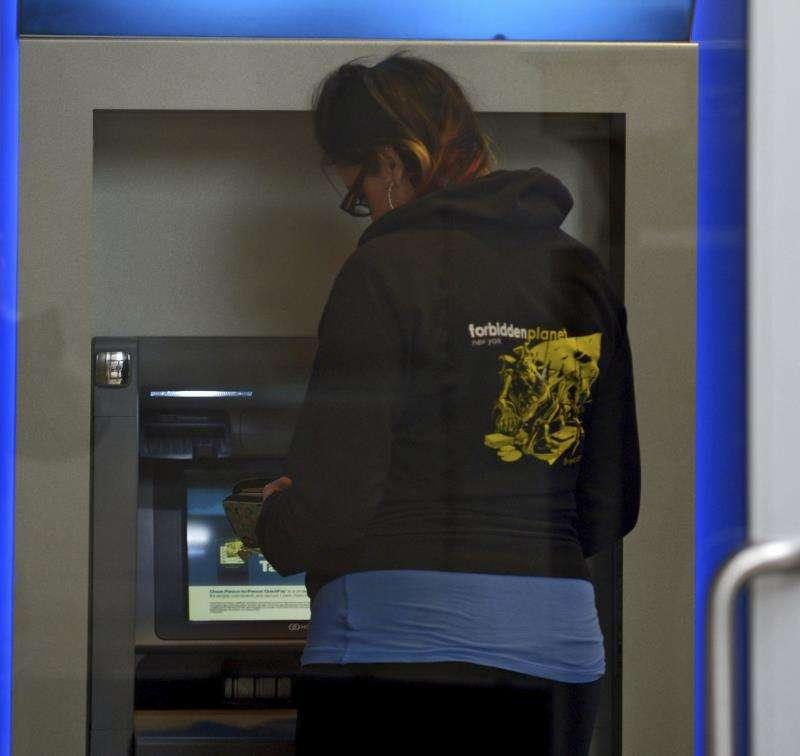 Una mujer retira dinero de un cajero. EFE/Archivo