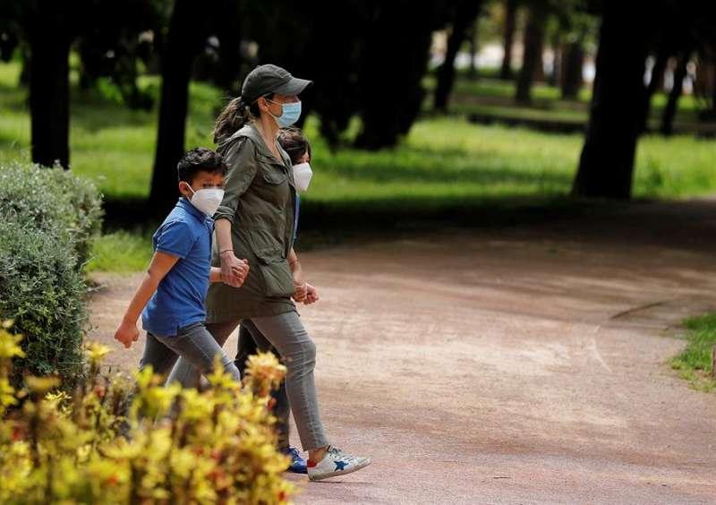 Una mujer pasea con dos niños por el jardín del río Turia. EFE