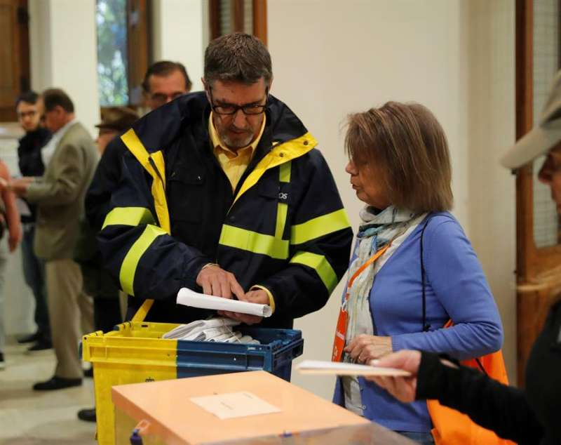 Un funcionario de Correos entrega a la presidenta de una mesa electoral votos emitidos por correo. EFE