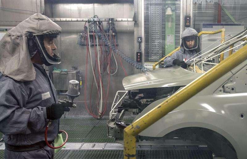 Dos trabajadores de la planta de pintura de Ford en Almussafes (Valencia), revisan una carrocería. EFE/Archivo