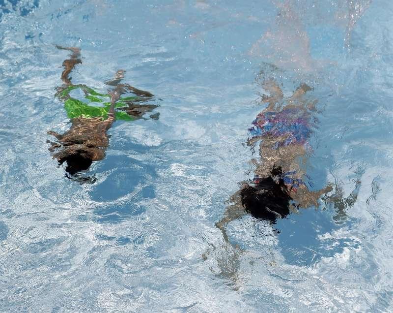 En la imagen, dos personas se refrescan en el interior de una piscin. EFE/J.J. Guillén/Archivo