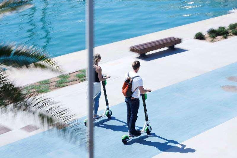 Dos usuarios de una de las empresas de alquiler de patinetes eléctricos en la Marina de València. EFE/Archivo