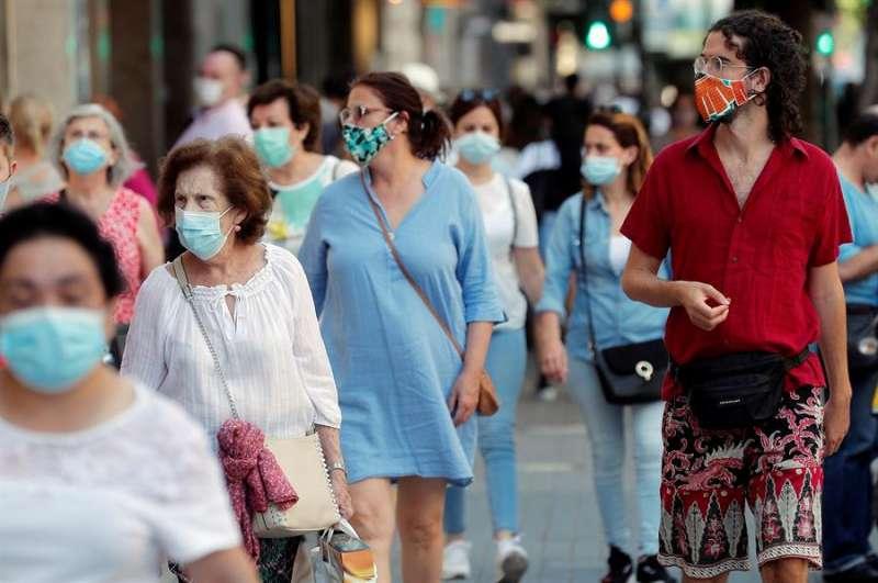 Varias personas caminan con mascarilla por un centro comercial.EFE