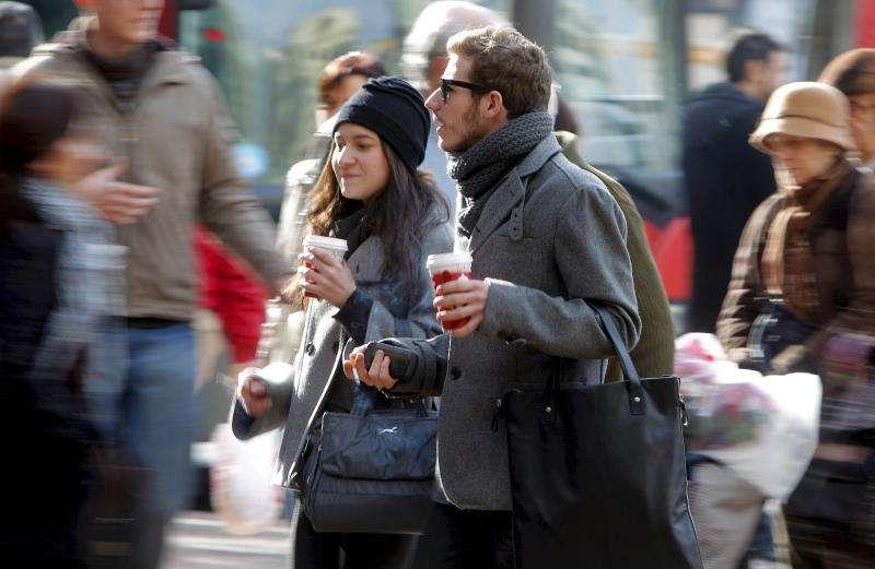 Dos jóvenes pasean con una bebida caliente en las manos. EFE/Archivo