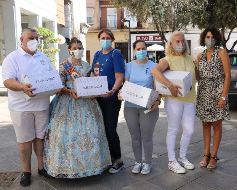 Cristina Mora con falleros y sus cajas de sobres de azúcar.