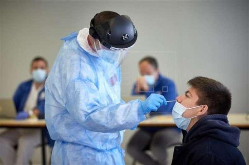 Profesionales sanitarios coge muestras a un estudiante para un PCR de covid. EFE/David Borrat/Archivo