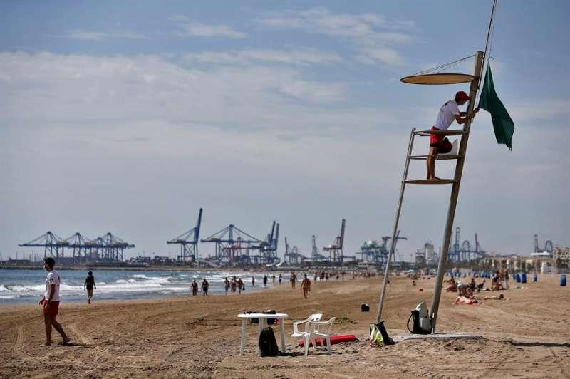 Un socorrista de la Cruz Roja iza la bandera verde en la playa de La Malvarrosa de València, el pasado 1 de junio. EFE