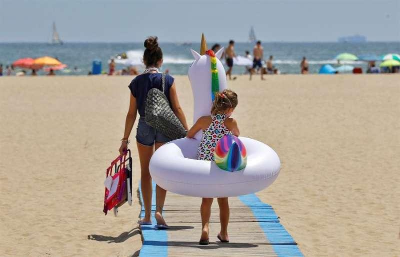 Una niña carga con su flotador hacia la orilla de la playa de Las Arenas de Valéncia, en un sábado marcado por el sol y las altas temperaturas. EFE/Manuel Bruque/Archivo