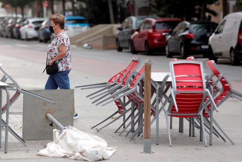 Una mujer pasa junto a una terraza recogida y con las sombrillas tumbadas por el viento. EFE