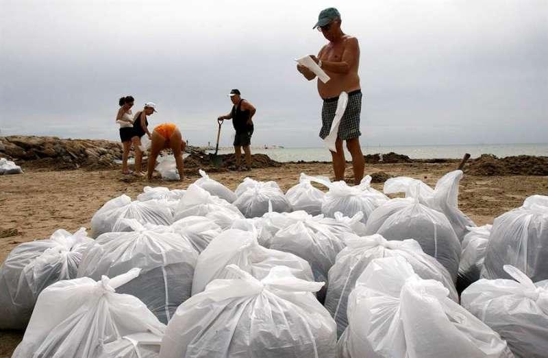 Varios voluntarios recogiendo residuos en una playa. EFE