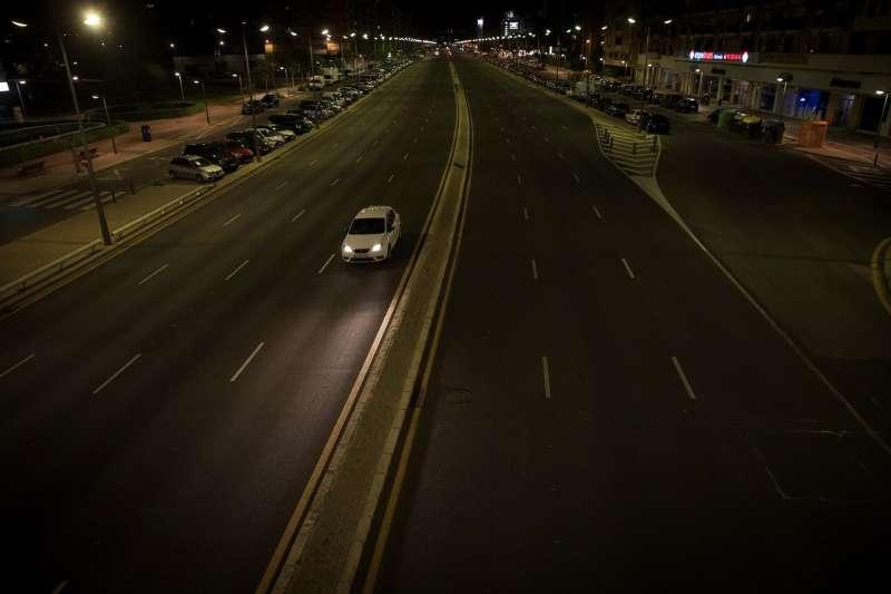 Un coche circula por una avenida de València durante la medianoche del sábado a falta de unos días para que finalice la vigencia del estado de alarma, el 9 de mayo, y las restricciones como el cierre perimetral, la limitación de aforos o el toque de queda necesiten de autorización judicial.