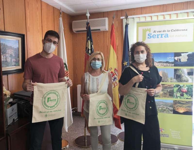 La alcaldessa, el regidor i  la presidenta de l?Associació de Comerciants i Empresaris de Serra amb les bosses serigrafiades. / EPDA