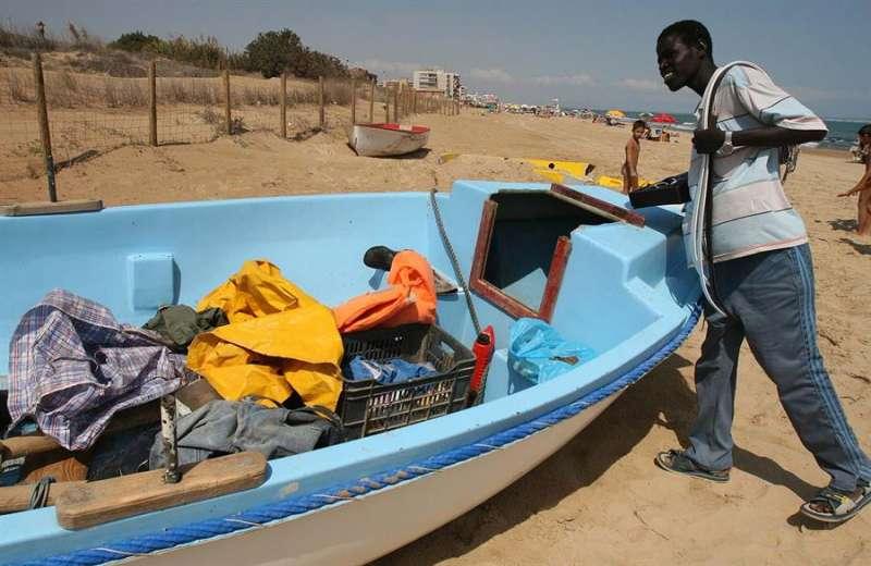 Un hombre junto a una patera localizada en Alicante, en una imagen de archivo. EFE