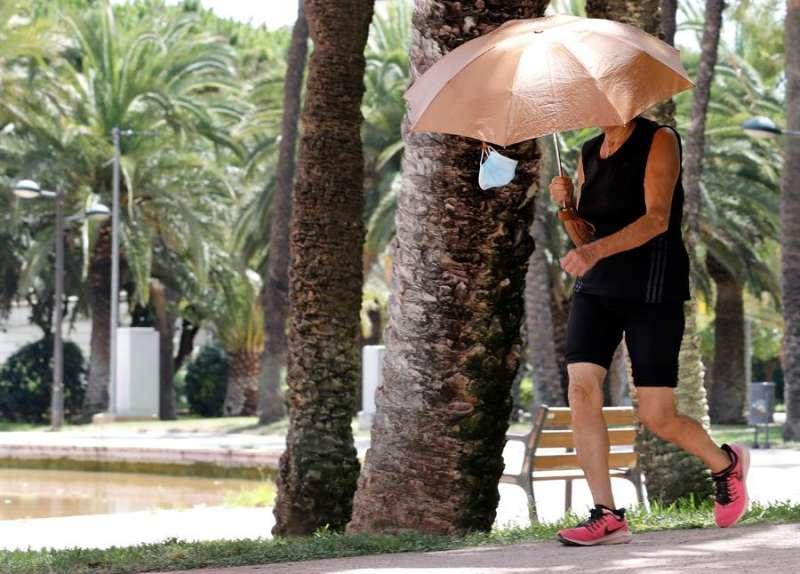 Una mujer se protege del son con un paraguas en el antiguo cauce del río Túria, en València. EFE/Juan Carlos Cárdenas/Archivo