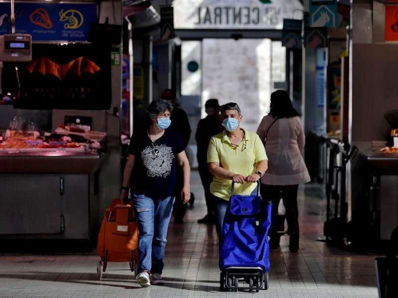 Dos mujeres realizan la compra con mascarilla. EFE