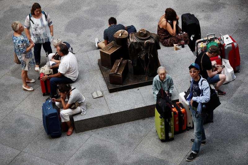 Viajeros en espera en la estación de Atocha de Madrid en el inicio del puente de agosto. EFE