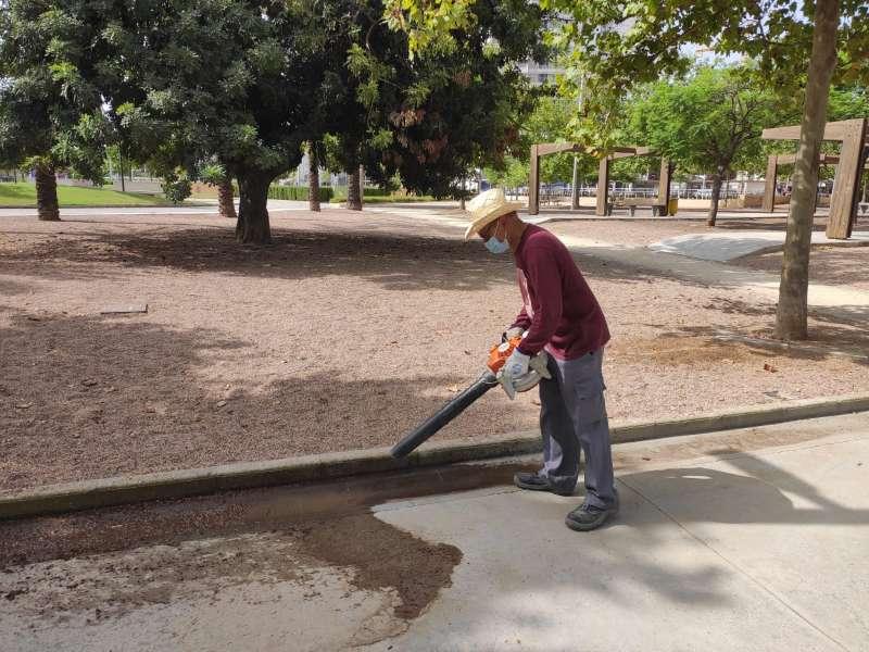 Un señor limpia un jardín en Torrent. EPDA