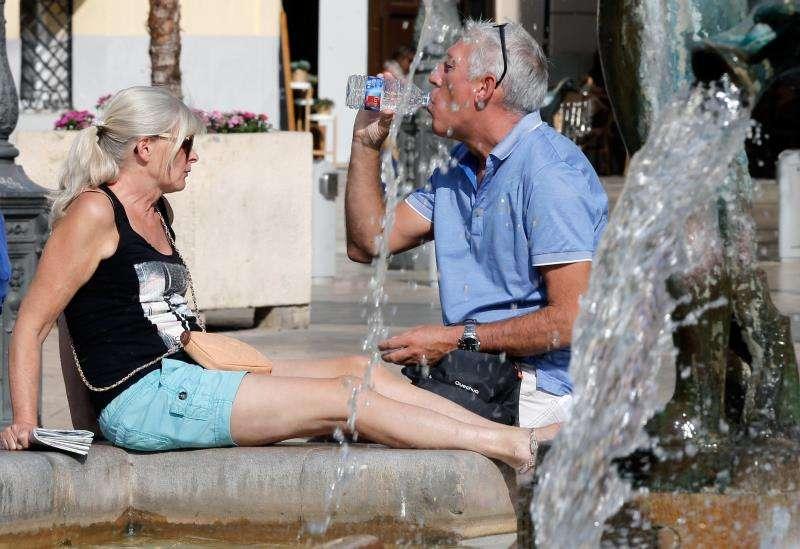 Una pareja de turistas se refresca en una fuente céntrica en València en un día caluroso. EFE/Archivo