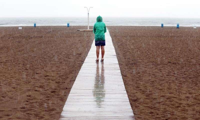 Una mujer contempla la playa de la Malvarrosa de València bajo la lluvia. EFE/Archivo