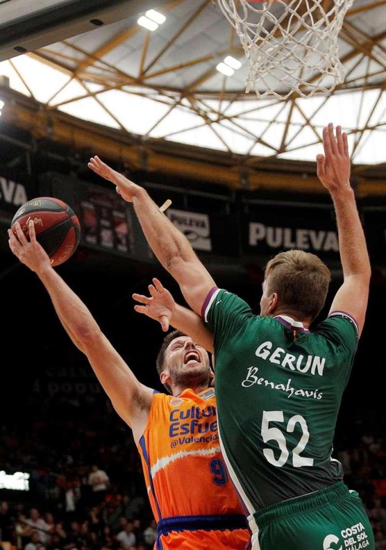 El base del Valencia Basket Sam van Rossom (i) trata de vencer la defensa del pívot del Unicaja Málaga Volodymyr Gerun durante el partido de la quinta jornada de la Liga Endesa. EFE/Kai Försterling