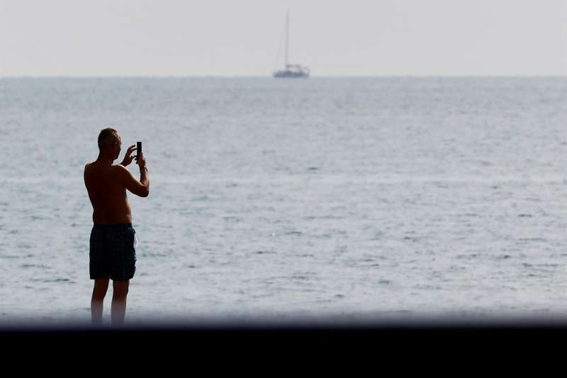 Una persona toma una foto desde la playa de la Malvarrosa.