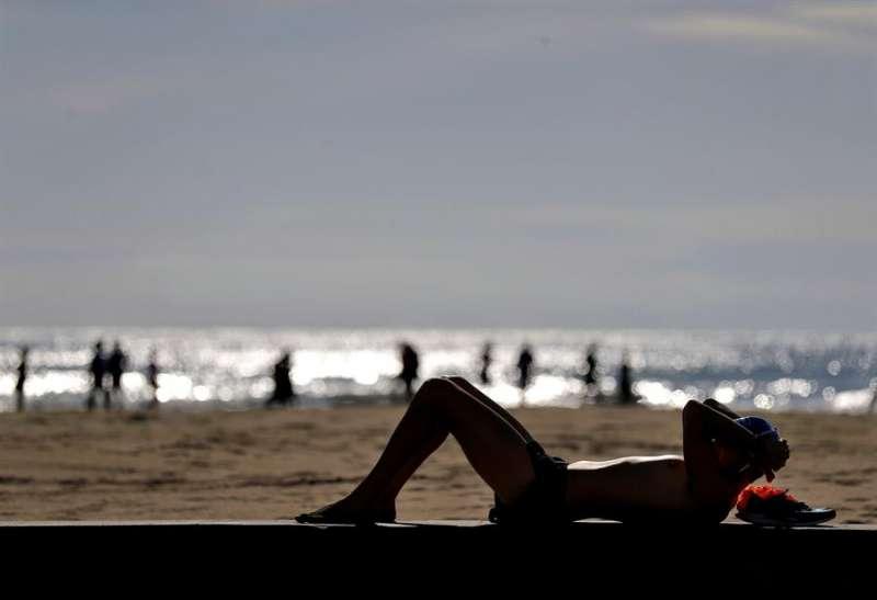 Una persona toma el sol en la playa de Alboraya. EFE