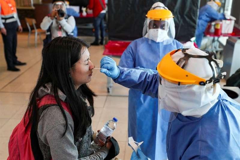 Personal médico realiza pruebas PCR en un aeropuerto. EFE