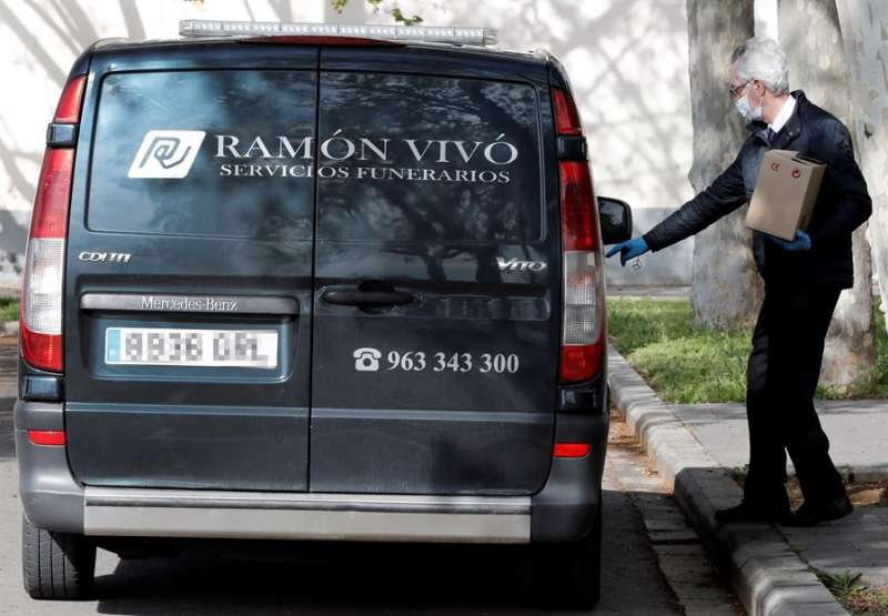 Un operario de una funeraria recoge las cenizas de un fallecido por covid-19 en el cementerio de Valencia. EFE