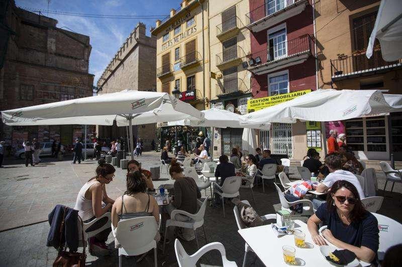 Varias personas toman algo en una terraza, en la plaza del doctor Collado junto a La Lonja de Valencia. EFE/Archivo
