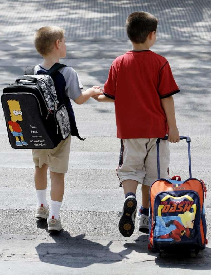Dos niños cargados con sus mochilas salen del colegio. EFE/Archivo