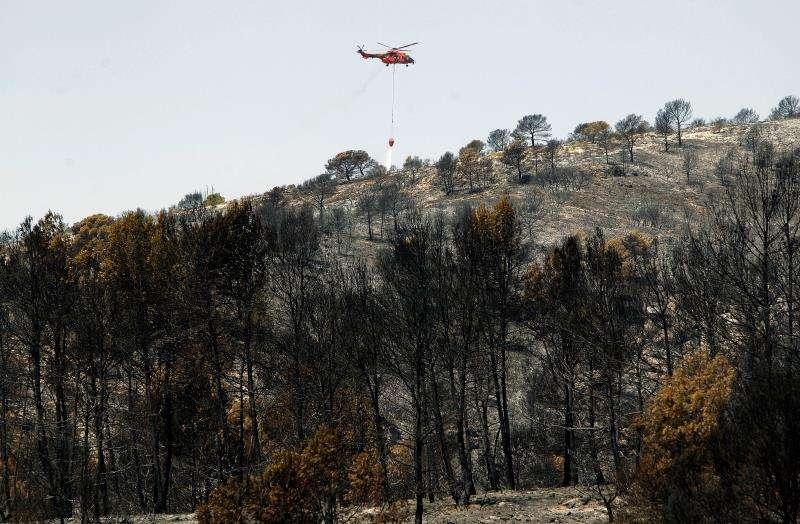Un helicóptero trabaja en la zona afecta por el incendio de Beneixama (Alicante). EFE/Archivo