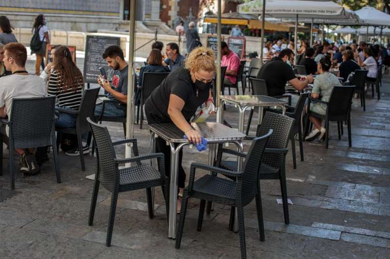 Una camarera desinfecta una mesa de una terraza. EFE/Biel Aliño/Archivo