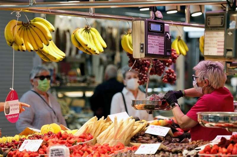 Varias personas protegidas con mascarillas, hoy, sexagésimo octavo día del estado de alarma, en el Mercado Central de Valencia. EFE