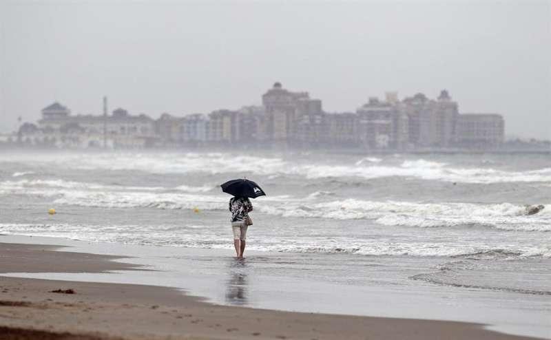 Una mujer pasea bajo un paraguas por la orilla de la playa de La Malvarrosa de Valènciaprotegiéndose de la lluvia. EFE/Manuel Bruque